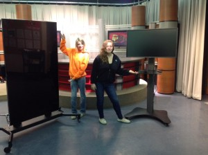 "Molly Fanning (l) and Shelby Giddings (r) stand beside 75"" vertical monitor and 42"" touch screen monitor."